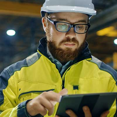 A Man in a Hardhat and yellow coat using IBM Maximo work orders and inspections.