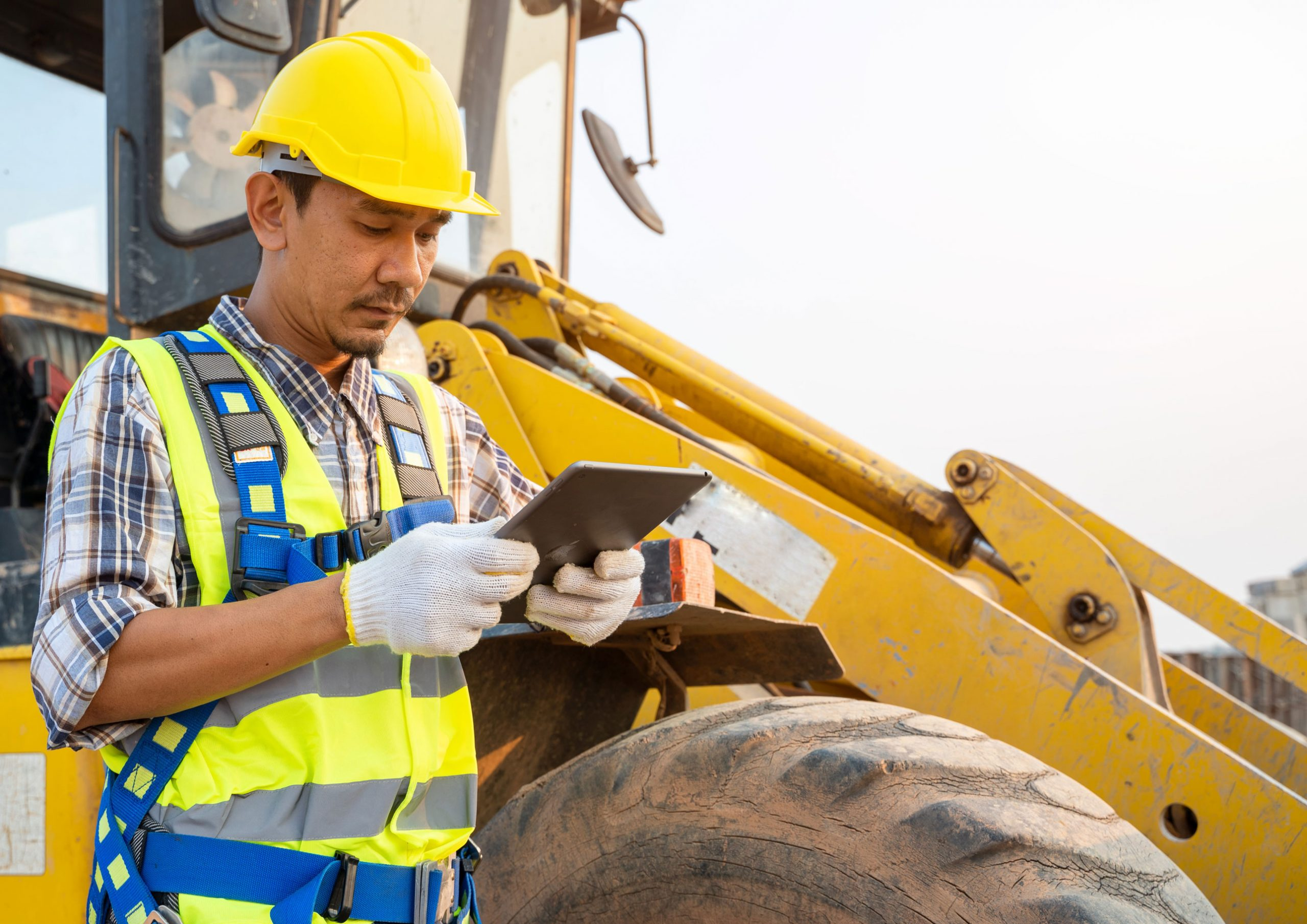 Man inspecting a vehicle with Maximo on a tablet
